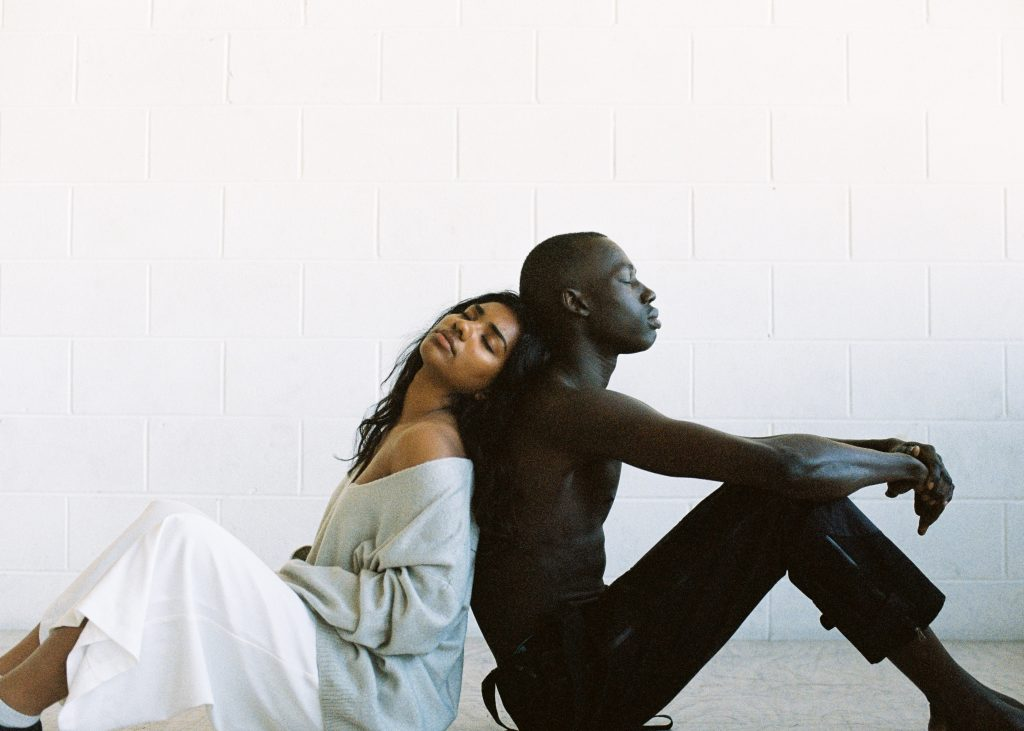 black man and woman leaning on one another